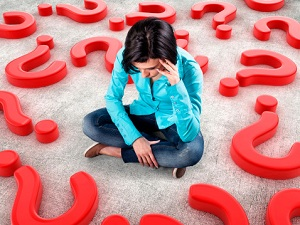 Woman sitting surrounded by question marks