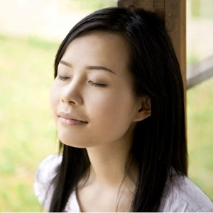 A woman closes her eyes and takes a moment to breathe.