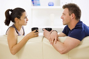 A couple having coffee together on a couch.