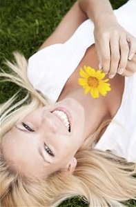 Woman laying in grass with flower