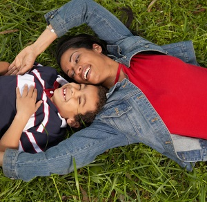 mother and her son lying on the grass