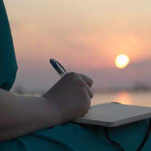 Woman writing in her diary at sunset