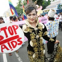 "Woman holds a ""Stop AIDS"" sign at World AIDS Day event"