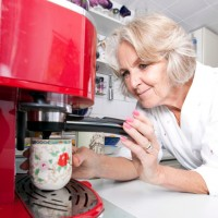 Senior woman makes a cup of coffee at home