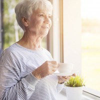 An elderly woman drinks coffee at her window