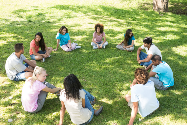 Friends sitting in a circle at park