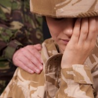 A female soldier cries while another soldier comforts her