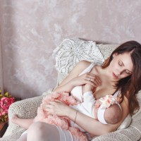 Mother breastfeeds her baby girl