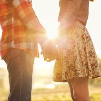Couple holding hands outside in sunlight