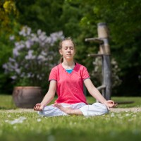 Young girl meditating outside on the grass