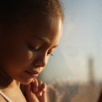 Sad young girl leaning next to a window