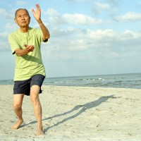Senior man practicing tai chi on the beach