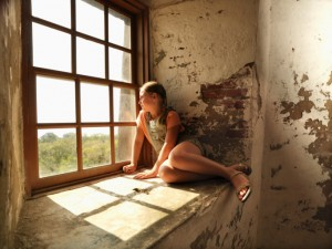 A young girl sitting on a window ledge looks out, lost in thought