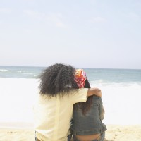 Rear view of couple hugging on beach