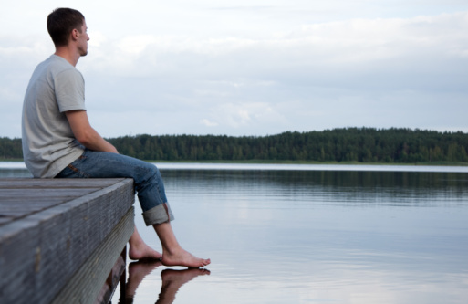 A young man sitting alone by the water
