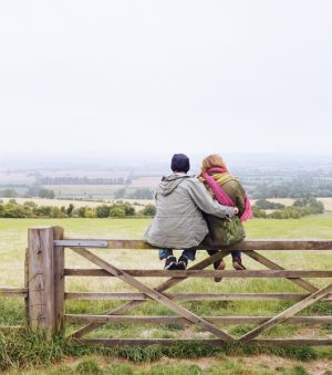 Two people sit on a fence overlooking a field. One person has an arm around the other person.