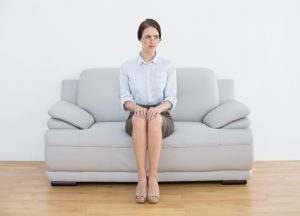 Person in business skirt sits on white sofa in room with serious expression