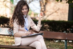 Young, smiling person in business attire sits on bench making notes in notebook
