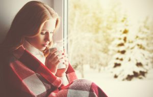 Person with long auburn hair sits in window, wrapped in red and white plaid blanket, inhaling steam from hot drink