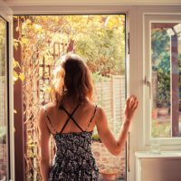Rear view of person with long hair in tank top standing in open doorway and looking outside
