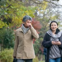 Two people dressed in autumn outerwear talk while walking along tree-lined path