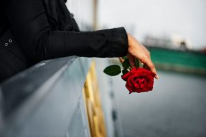 Person in black coat holding rose