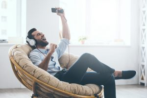 young man in headphones gesturing and keeping eyes closed while listening to music in big comfortable chair at home