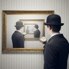 A man holding a small clock looks at a painting with a repeating mirror image of himself.