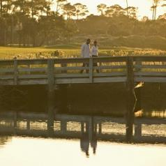 Couple walking over a bridge at sunset
