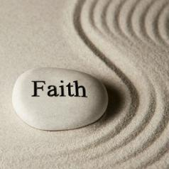 "A rock that says ""faith"" on it sits in sand that has been raked into a wavy design."
