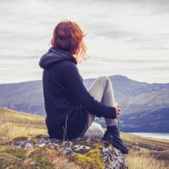 Woman surveys the view from atop a hill.