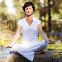 A woman sits outside in a peaceful area and meditates.