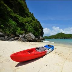 A kayak is sitting on a sandy beach, a few yards away from the water.