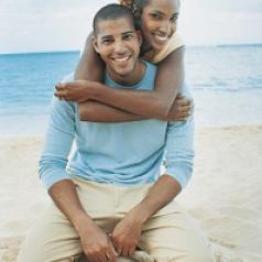Young black couple on sandy beach. Both are smiling and kneeling on the sand. She has her arms wrapped around his shoulders from behind him.