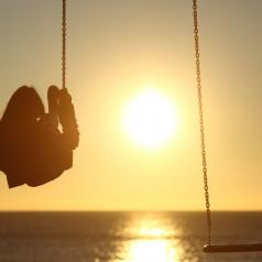 Rear view of a person on swing over the ocean