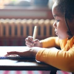 Young girl writing in notebook