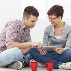Two people sit on floor and look over schedule on tablet. A red mug sits in front of each person.