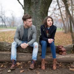 Couple sits apart on bench under tree on cold day