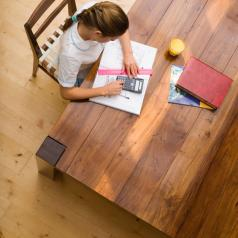 Overhead view of preteen student does homework at kitchen table with school supplies spread around