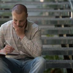 Person in button-down shirt sits on stairs, holding a pen and looking thoughtfully down into small notebook