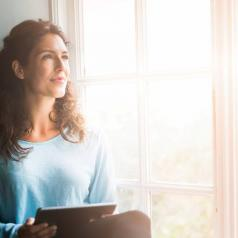 Person with long wavy hair holds tablet while sitting in window seat and looks up from it to outside a sunlit window