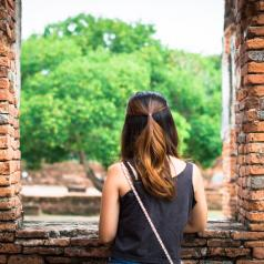 Person looking out brick window