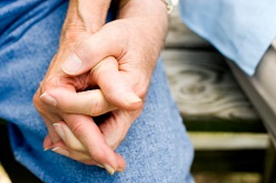 A close-up of a couple's hands clasped as they are seated side-by-side