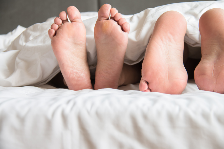 The feet of two people sticking out from covers