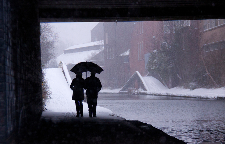 Couple walks out from under bridge into snow with shared umbrella