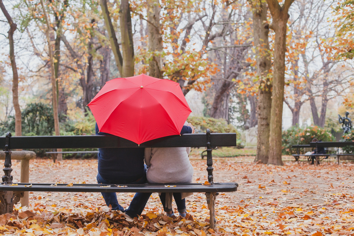 Rear view of couple seated on park bench, in close contact, red umbrella hiding their heads from view