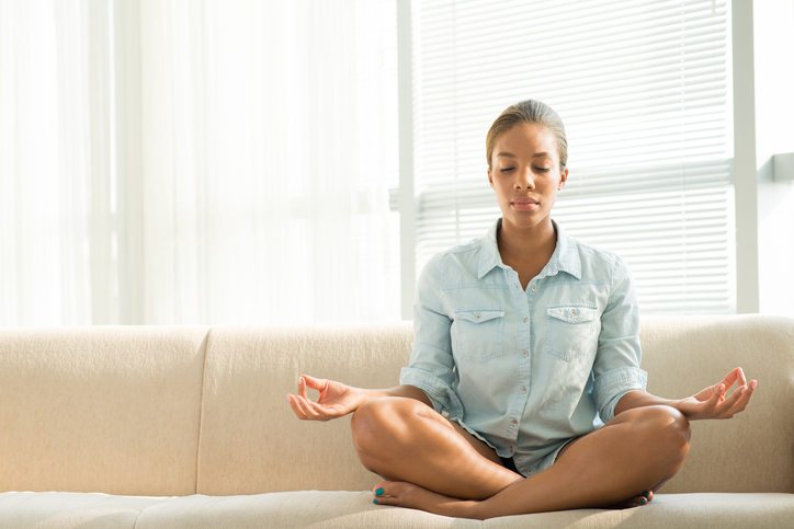 Young adult sits cross-legged in mediation pose on sofa