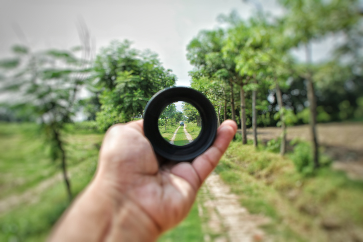 Outstretched hand holds lens that shows clear focus of tree-lined road