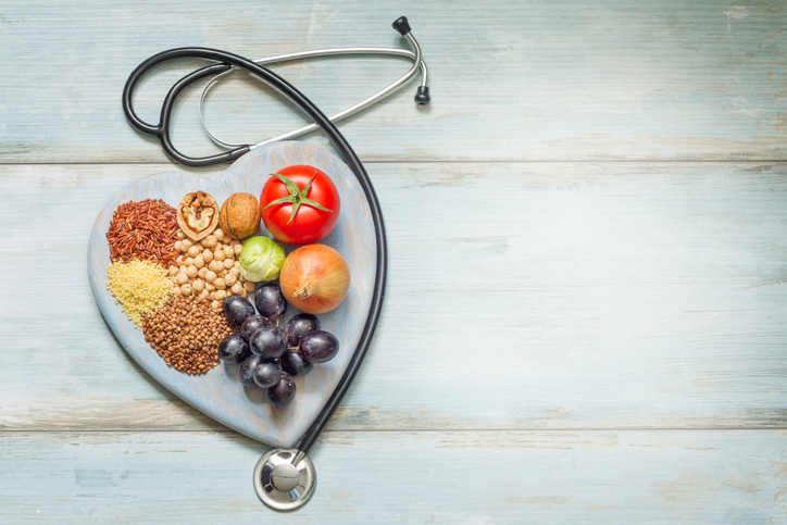 fresh produce and grains surrounded by stethoscope in shape of heart