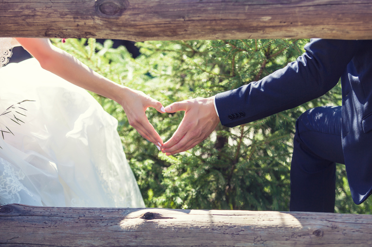 Hands of couple in wedding clothing form heart